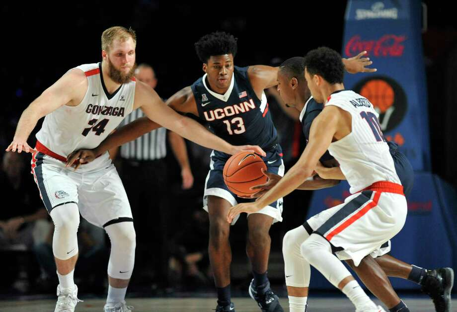 Gonzaga center Przemek Karnowski (24), and UConn forward Steve Enoch (13) look on as Sterling Gibbs scoops up a loose ball in front of Gonzaga guard Bryan Alberts (10) during the Huskies' 73-70 loss on Friday in the Battle 4 Atlantis in the Bahamas. Photo: Brad Horrigan — The Associated Press  / Hartford Courant