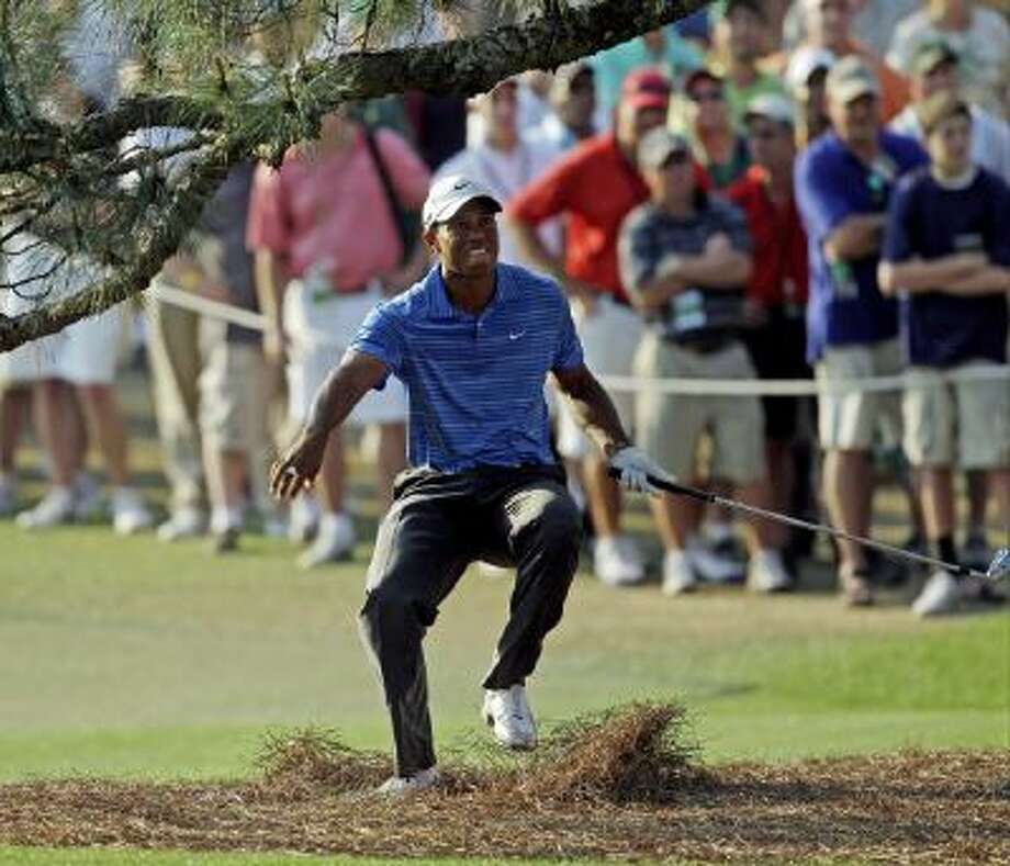 In this April 9, 2011, file photo, Tiger Woods nearly falls backward after hitting out of the rough under the Eisenhower Tree on the 17th hole during the third round of the Masters golf tournament in Augusta, Ga.