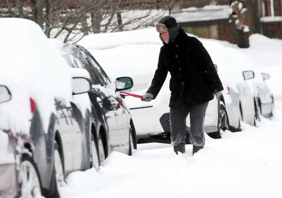 Laura Noe of Branford clears snow from her car Wednesday morning January 22, 2014, on Wilford Avenue in Branford. Photo: Peter Hvizdak — New Haven Register  / ©Peter Hvizdak /  New Haven Register