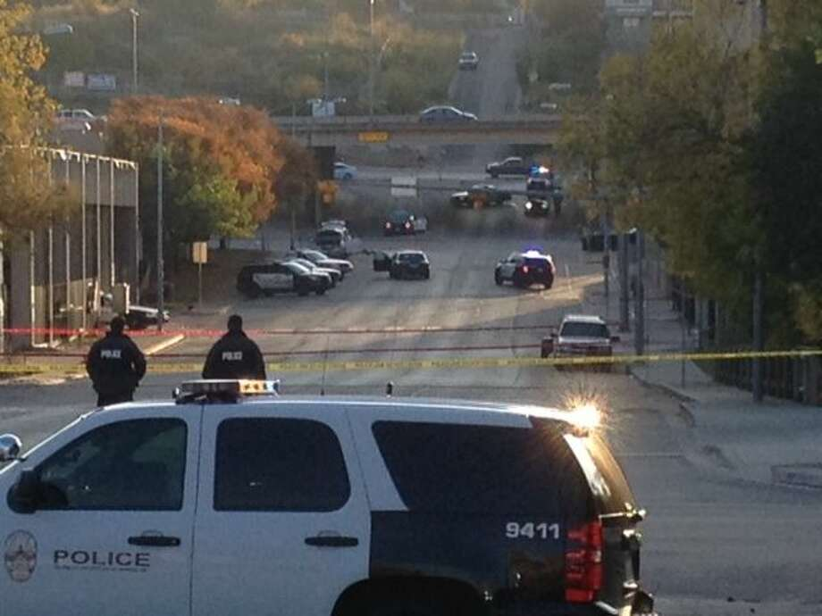 Police tape marks off the scene after authorities shot and killed a man who they say opened fire on the Mexican Consulate, police headquarters and other downtown buildings early Friday in Austin, Texas. In the distance, police cars surround the suspect's vehicle parked near the Interstate 35 overpass. Photo: Associated Press  / ap