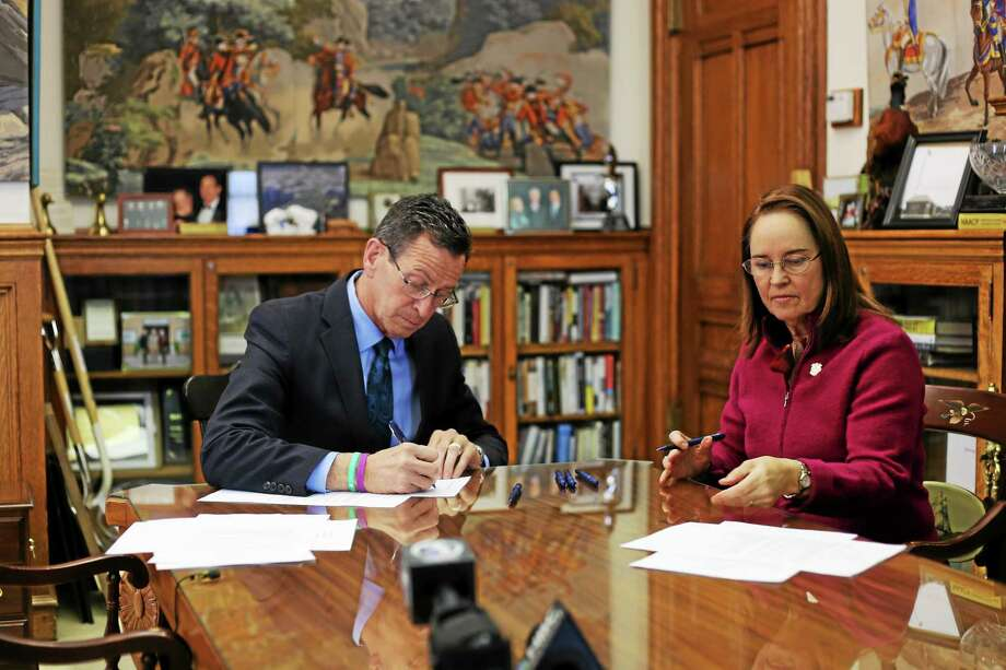 Gov. Dannel P. Malloy signs the executive order that bans state-funded travel to Indiana over its passage of the Religious Freedom Restoration Act and Secretary of the State Denise Merrill gets ready to make it official Photo: (CT New Junkie)