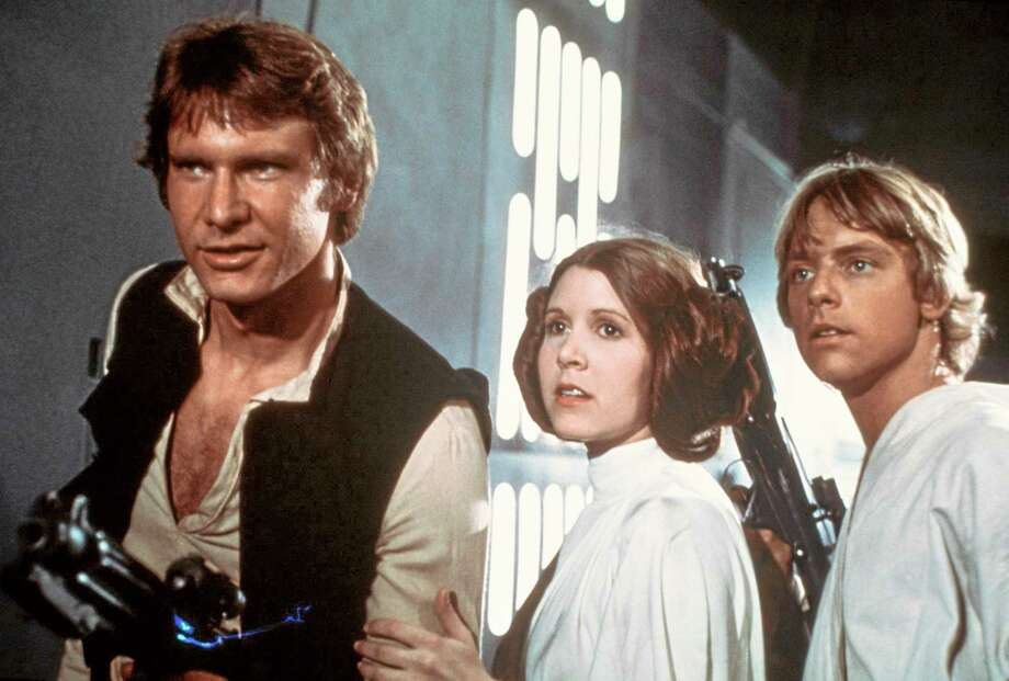 """In this 1977 image provided by 20th Century-Fox Film Corporation, from left, Harrison Ford, Carrie Fisher, and Mark Hamill are shown in a scene from """"Star Wars"""" movie released by 20th Century-Fox.  From the set of ìStar Wars: Episode VIIî in Abu Dhabi, director J.J. Abrams announced the launch of Star Wars: Force for Change, a campaign to raise funds for United Nations Childrenís Fundís (UNICEF).  The campaign will run from 12:01 a.m. PDT on May 21, 2014, until 11:59 p.m. PDT on July 18. (AP Photo/20th Century-Fox Film Corporation) Photo: AP / 20th Century-Fox Film Corporation"""