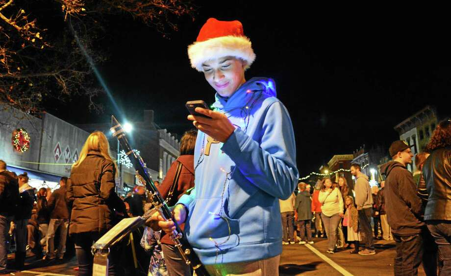 His performance complete, a Middletown High School Marching Band clarinetist finally can get to the important stuff — checking messages — in front of the Middlesex County Chamber of Commerce. Photo: Cassandra Day — The Middletown Press