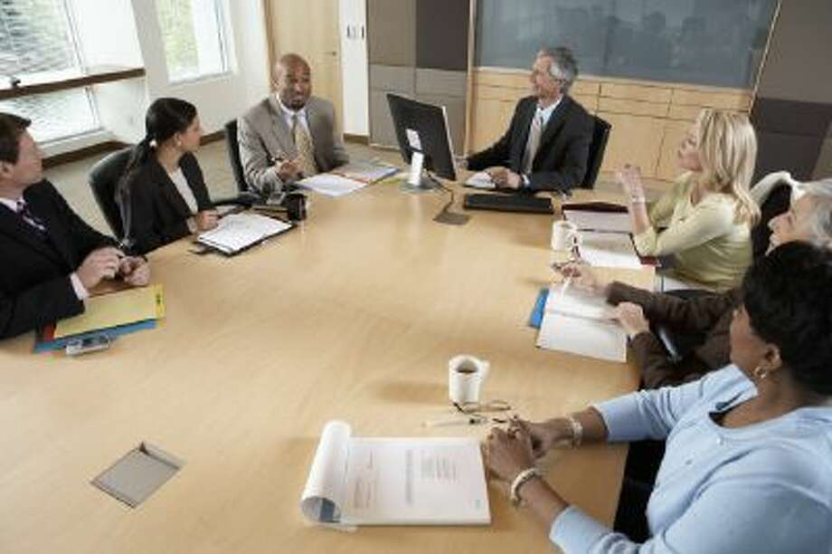 Business executives holding a meeting in a boardroom.