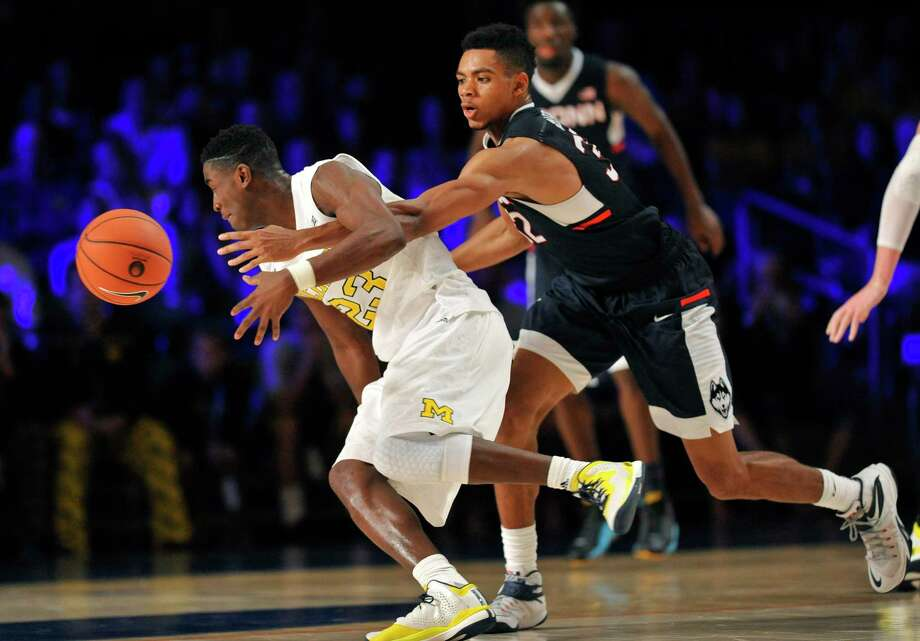 Connecticut forward Shonn Miller (32) pokes the ball away from Michigan guard Caris LeVert (23) during an NCAA college basketball game Wednesday, Nov. 25, 2015, in Paradise Island, Bahamas. Photo: Brad Horrigan/The Courant Via AP / The Courant