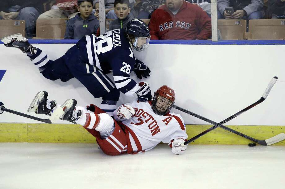 Yale's Ryan Hitchcock and Boston University's Cason Hohmann battle along the boards during the Terriers' 3-2 overtime win in Friday's NCAA tournament regional semifinal game in Manchester, N.H. Photo: Elise Amendola — The Associated Press  / AP