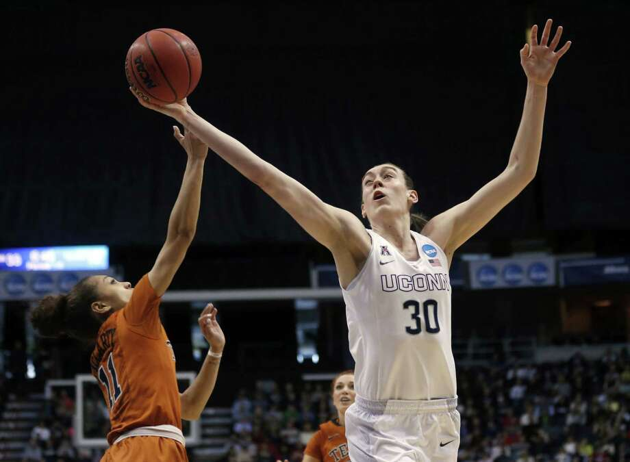 UConn's Breanna Stewart grabs a rebound over Texas' Brooke McCarty during the first half of the Huskies' 105-54 win Saturday in Albany, N.Y. Photo: Mike Groll — The Associated Press  / AP