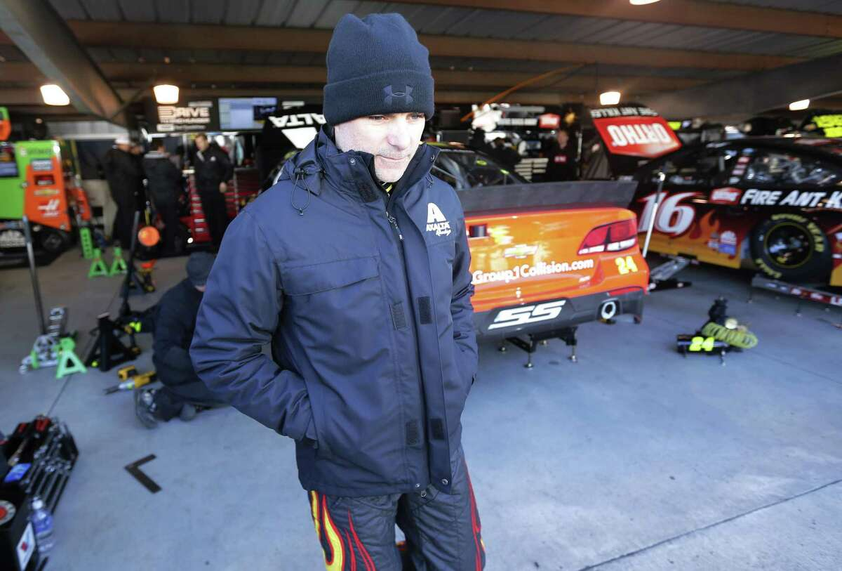 Driver Jeff Gordon is bundled up for the cold Saturday as he leaves the garage after practice for the NASCAR Sprint Cup race at Martinsville Speedway in Martinsville, Va.