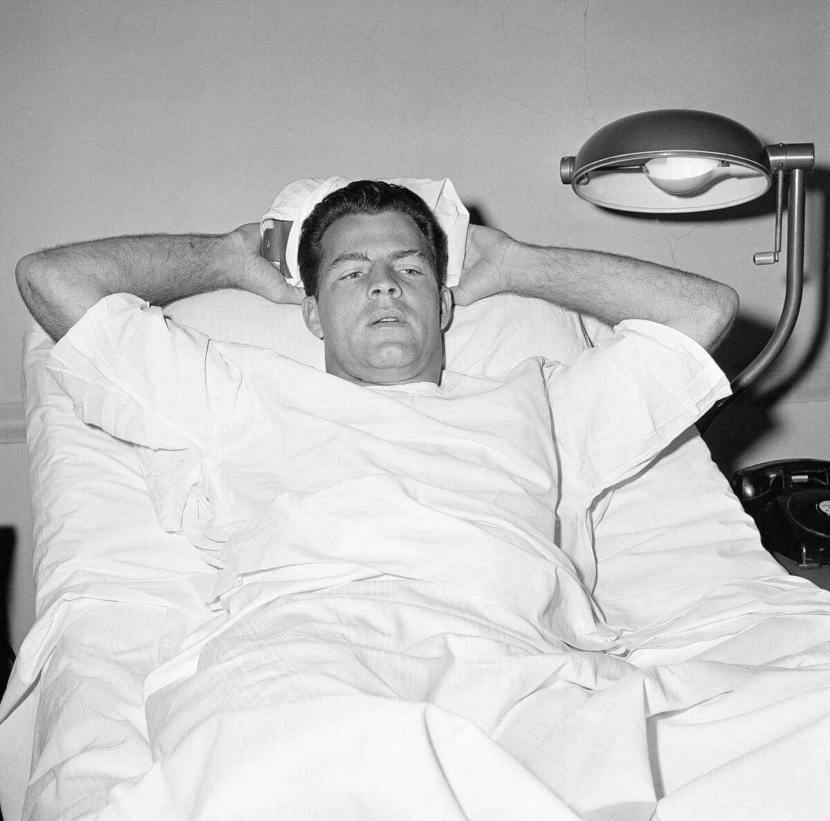 In this Nov. 22, 1960 file photo, New York Giants player Frank Gifford lies in a bed holding an ice pack on his head at St. Elizabeth's Hospital in New York.