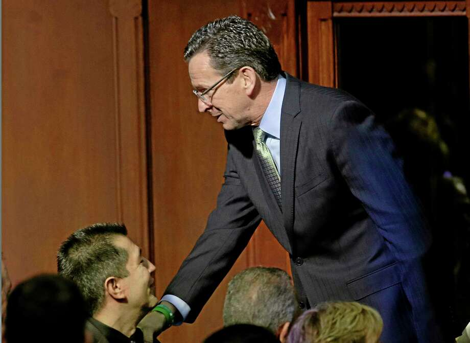 Connecticut Gov. Dannel P. Malloy shakes hands on the way out of the House Chamber after delivering his 2014 State of the State address in front of a joint session of the legislature at the Capitol in Hartford, Conn., Thursday, Feb. 6, 2014. (AP Photo/Stephan Savoia) Photo: AP / AP
