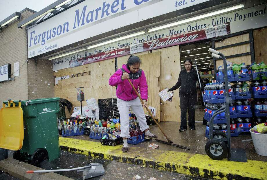 Anjana Patel cleans up the damage from Monday's riots at her store, Ferguson Market and Liquor, Wednesday, Nov. 26, 2014, in Ferguson, Mo.  A grand jury's decision not to indict a police officer in the shooting death of an unarmed 18-year-old has stoked passions nationwide, triggering debates over the relations between black communities and law enforcement.  (AP Photo/David Goldman) Photo: AP / AP