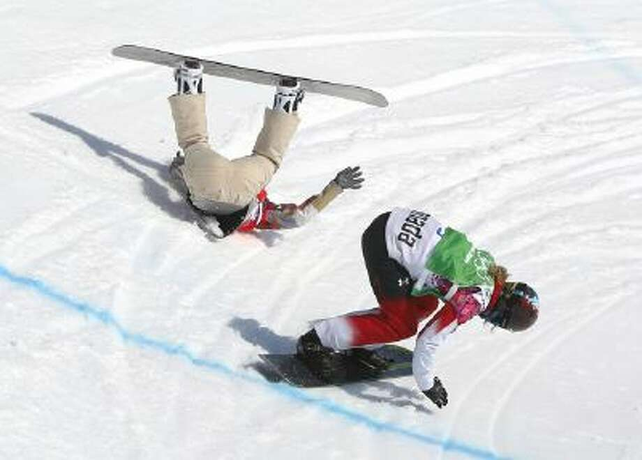 Lindsey Jacobellis of the United States crashes in the women's snowboard cross semifinal as Canada's Dominique Maltais. tries to avoid her at the Rosa Khutor Extreme Park, at the 2014 Winter Olympics, Sunday, Feb. 16, 2014, in Krasnaya Polyana, Russia.