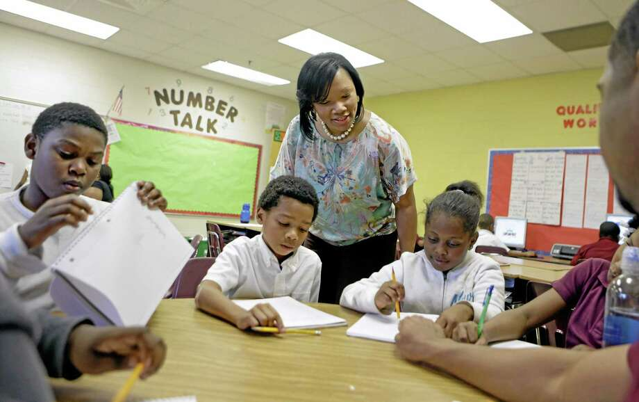 FILE - In this April 18, 2013, file photo, Burgess-Peterson Elementary School principal Robin Robbins, center, meets with students during an after-school study program in Atlanta, in preparation for state standardized testing, soon to begin. A new poll from the Associated Press-NORC Center for Public Affairs Research finds parents of school-age children view standardized tests as a useful way to track student progress and school quality. Most parents say their own children are given about the right number of standardized tests, according to the AP-NORC poll. And almost three quarters say they favor changes that would make it easier for schools to fire poorly performing teachers. (AP Photo/David Goldman) Photo: AP / AP