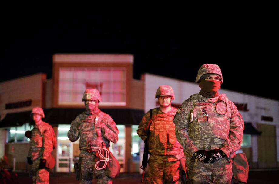 Missouri National Guard stand watch outside a Walgreens store, Wednesday, Nov. 26, 2014, in Ferguson, Mo. Missouri's governor ordered hundreds more state militia into Ferguson on Tuesday, after a night of protests and rioting over a grand jury's decision not to indict police officer Darren Wilson in the fatal shooting of Michael Brown, a case that has inflamed racial tensions in the U.S. (AP Photo/David Goldman) Photo: AP / AP