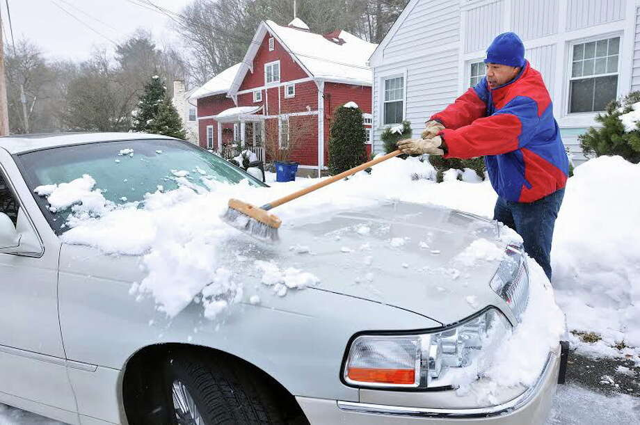 (Peter Casolino/New Haven Register)  Earl Vaughn clears off his car, still covered in snow from Thursdays storm, as snow beings to fall early Saturday afternoon in New Haven. pcasolino@NewHavenRegister Photo: Journal Register Co.