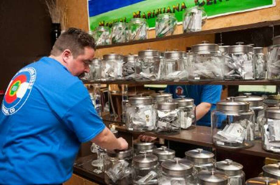 Sam Walsh sets up marijuana products at a store in Denver. Banks can now give loans to marijuana-related businesses. Photo: Getty Images / 2014 Getty Images