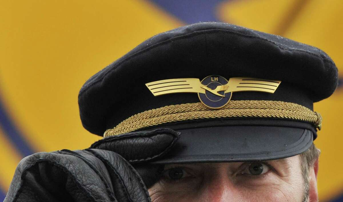 FILE - In this Feb. 22, 2010 file picture, a Lufthansa Airlines pilot holds the brim of his cap at the airport in Frankfurt, Germany. Carsten Spohr, CEO Lufthansa _ the parent company of Germanwings _ says his pilots undergo yearly medical examination but that doesn't include psychological tests.