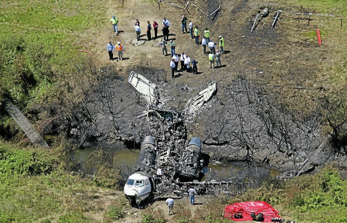 This aerial photo shows wreckage from where a plane plunged down and erupted in flames during a takeoff attempt at Hanscom Field on Saturday night, Monday, June 2, 2014, in Bedford, Mass. Lewis Katz, co-owner of The Philadelphia Inquirer, and six other people died in the crash. (AP Photo/The Boston Globe, David L. Ryan) BOSTON HERALD OUT, QUINCY OUT; NO SALES MANDATORY CREDIT.