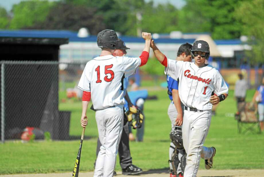 Cromwell senior Kevin Radziewicz (1) gets a high-five from senior Jake Regula (15) after crossing home plate in the Panthers tourney opener at Monnes Field. Photo: Jimmy Zanor — Middletown Press