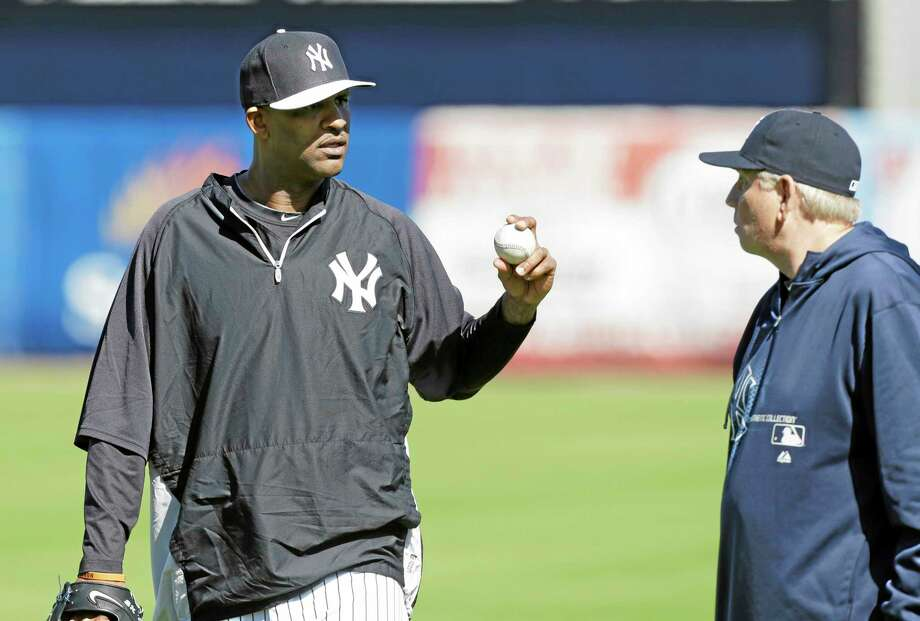 New York Yankees pitcher CC Sabathia talks with pitching coach Larry Rothschild during practice on Friday in Tampa, Fla. Photo: Charlie Neibergall — The Associated Press  / AP