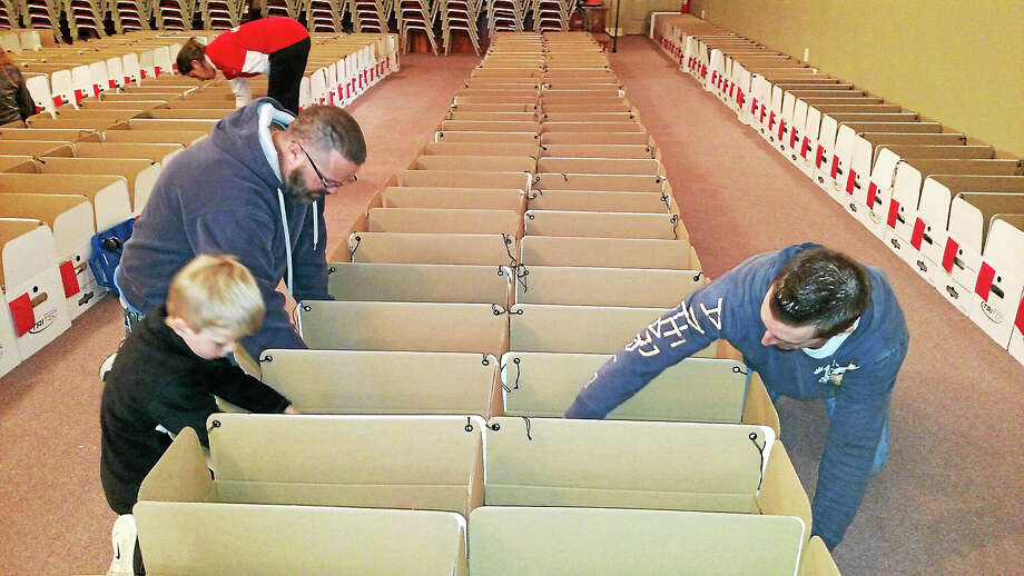 Ed Hickman and Timothy Hickman, 6, of Higganum, and Rich Pancoast, of Middletown, assemble Thanksgiving baskets for the Middletown Community Thanksgiving Project at Fellowship Church on Monday. Photo: Courtesy Jennifer Sprague