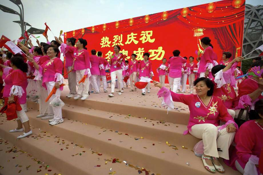 Participants celebrate following the announcement that Beijing will host the 2022 Winter Olympics at a gathering outside the Beijing Olympic Stadium, also known as the Birds Nest, in Beijing, Friday. Photo: AP Photo/Mark Schiefelbein / AP