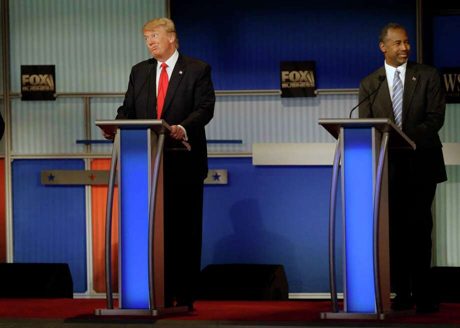 Donald Trump, left, and Ben Carson react during the Republican presidential debate at the Milwaukee Theatre Nov. 10, in Milwaukee. Photo: Jeffrey Phelps — The Associated Press  / FR59249 AP