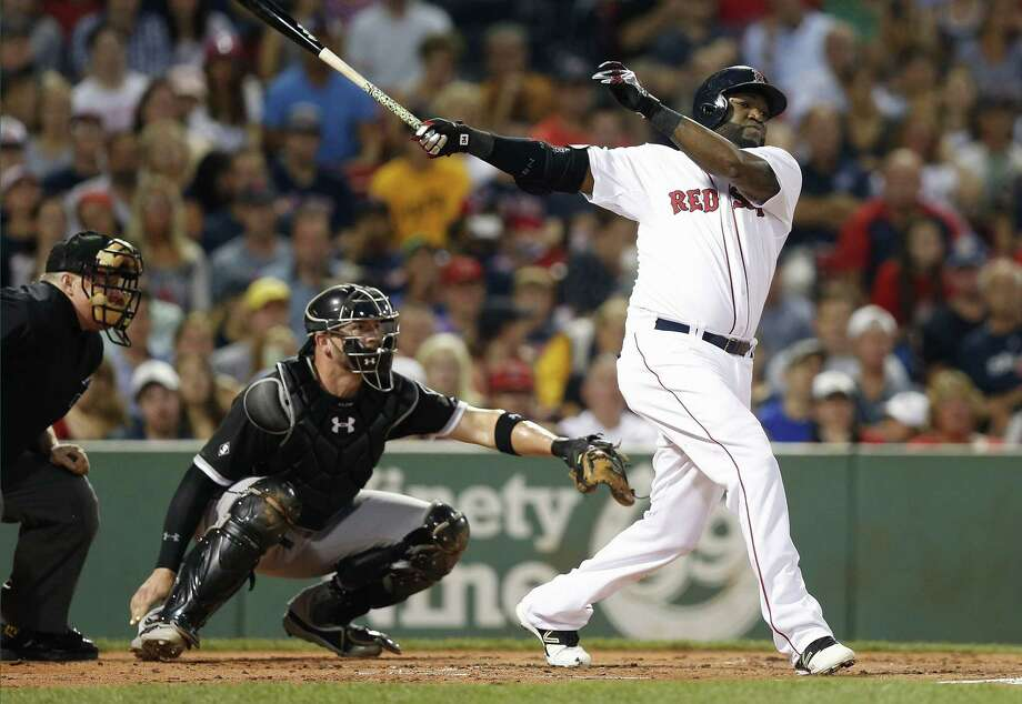 Boston Red Sox's David Ortiz, right, follows through on an RBI double in front of Chicago White Sox's Tyler Flowers during the first inning of a baseball game in Boston, Thursday, July 30, 2015. (AP Photo/Michael Dwyer) Photo: AP / AP