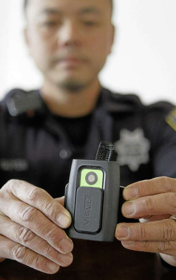 In this June 16, 2011, file photo, Oakland Police officer Huy Nguyen shows a video camera worn by some officers in Oakland, Calif., to record street encounters. Photo: Ap File Photo  / AP
