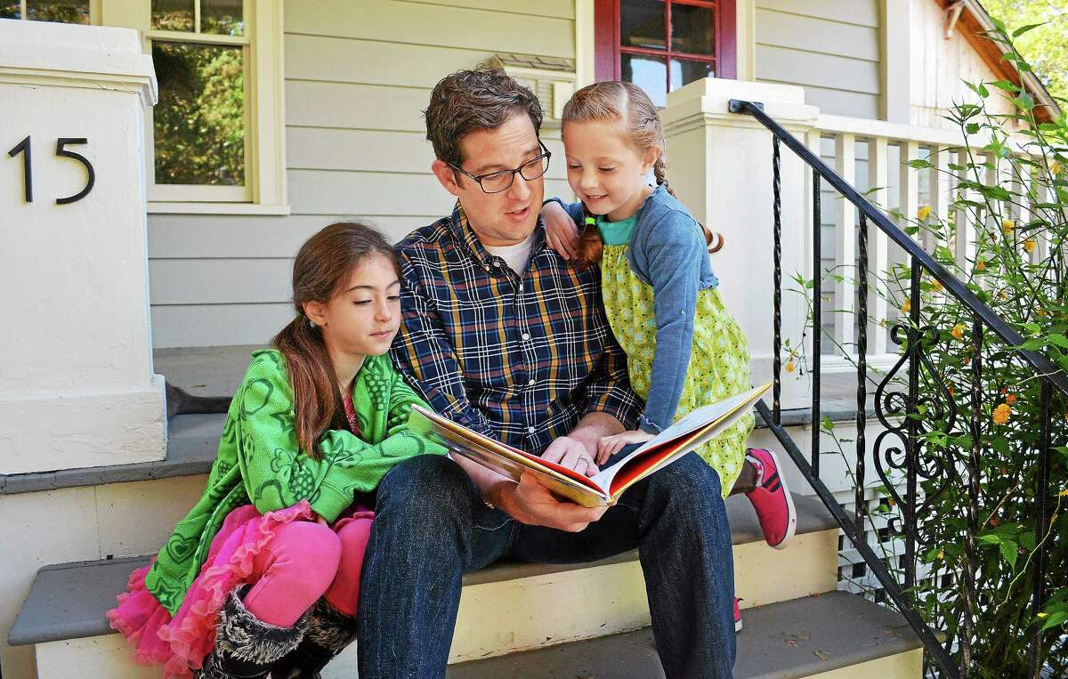 """Catherine Avalone — The Middletown Press Jeff Cohen, a public radio reporter at WNPR 90.5-FM, is the author of a children's book, """"Eva and Sadie and the Worst Haircut EVER!"""" Cohen reads the book to his daughters, Sadie, 8, left and Eva, 6, on the porch of their Middletown home Friday morning. The book is based on a true story about the time Sadie cut her little sister's hair."""