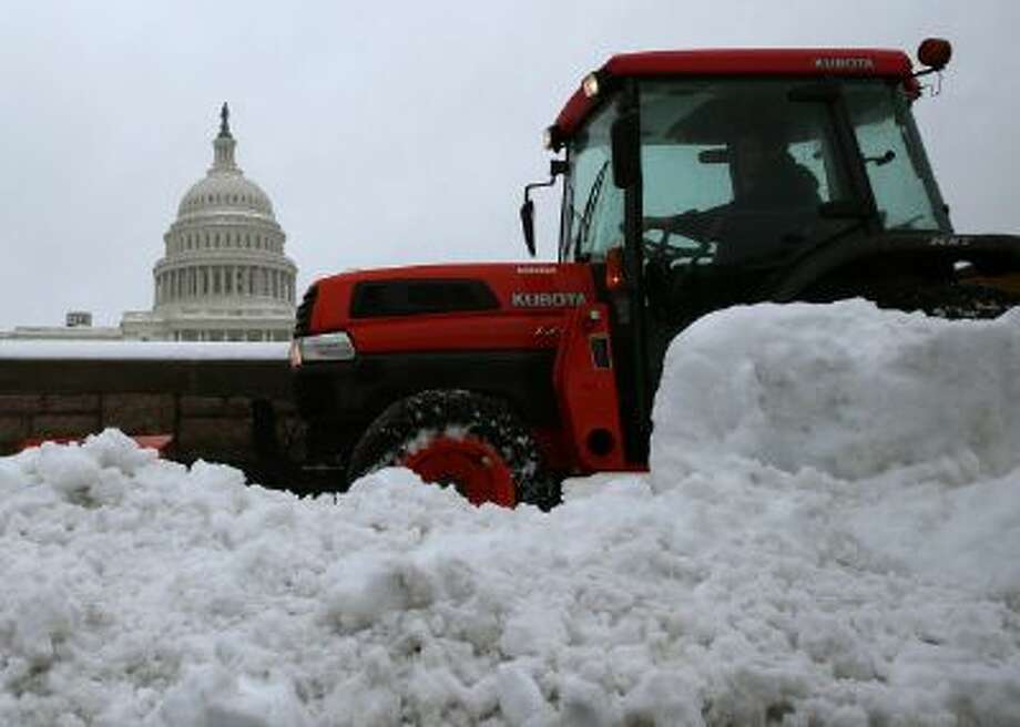 A tractor plows snow near the U.S. Capitol on Wednesday. The snow may have helped Congress reach a deal on the debt ceiling. Photo: Getty Images / 2014 Getty Images
