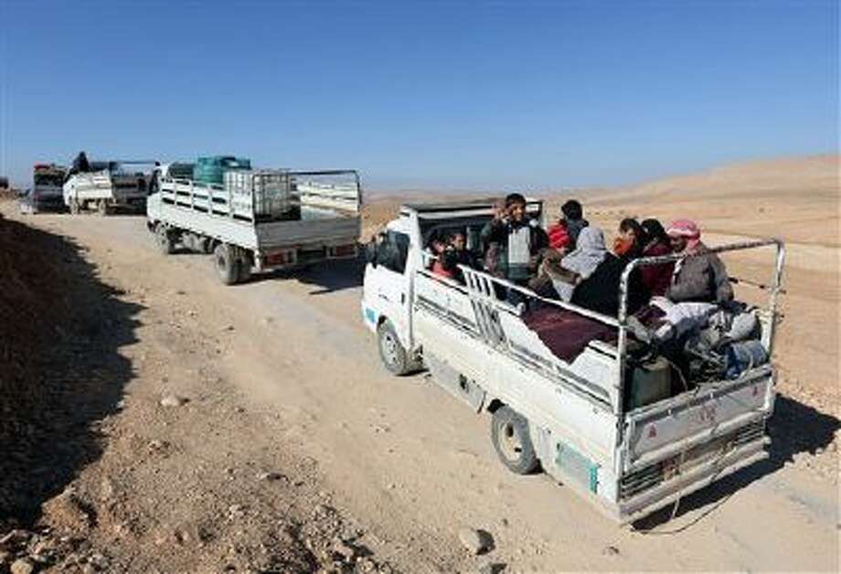 Syrian citizens with their belongings in trucks flee Yabroud, the last rebel stronghold in Syria's mountainous Qalamoun region, as they drive toward the Lebanese-Syrian. Photo: AP / AP