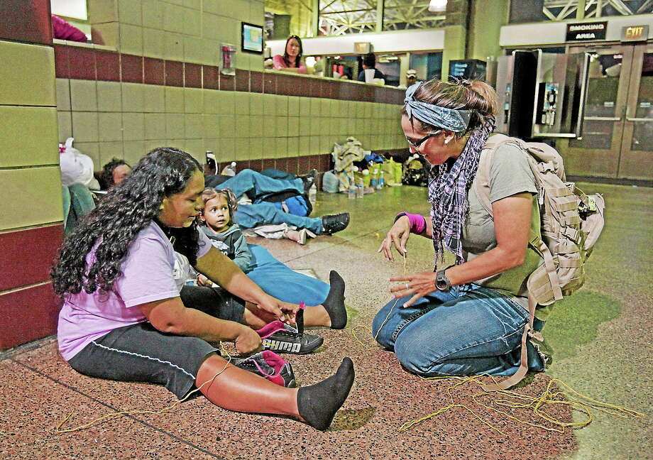 Volunteer Michelle Lewis of Phoenix, right, helps Doris Suyapa, of Honduras, with her shoes, by using yellow rope for shoe laces on May 29, 2014 at the Greyhound bus terminal in Phoenix. Photo: AP Photo/Rick Scuteri  / FR157181 AP