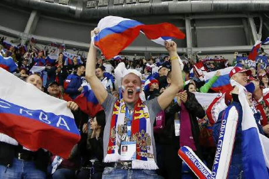 Russian hockey fans celebrate the women's team, Thursday, Feb. 13, 2014, in Sochi, Russia.