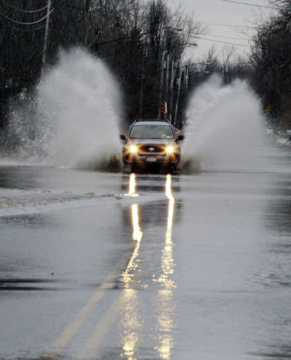 A vehicle blasts its way through a flooded Stony Road, Tuesday, Nov. 25, 2014, in Lancaster, N.Y. Western New York has localized flooding from melting snow following last week's lake-effect snow. (AP Photo/Gary Wiepert)