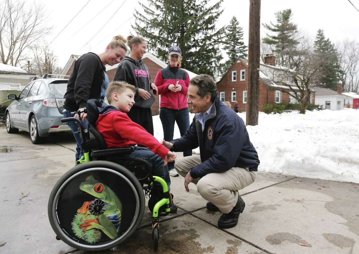 New York Gov. Andrew Cuomo greets Charlie Kelly III while surveying the aftermath of last week's lake-effect snowstorms on Monday, Nov. 24, 2014, in West Seneca, N.Y. Also pictured are is Charlie's mother Jodi Kelly and neighbors Kendyl Williams and Jen McNaughton. (AP Photo/Mike Groll)
