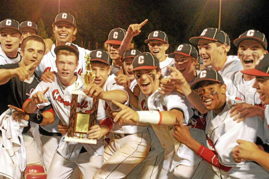 Members of the Cromwell baseball team celebrate their 2-1 win over East Hampton in the SLC championship game Saturday night at Dodd Stadium. Photo: Jimmy Zanor — The Middletown Press