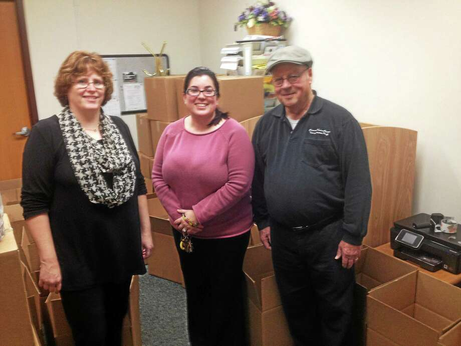 From left are Cromwell food bank personnel Lisa Olson, human services assistant, Joy Hollister, human services director, Al Fontenault, Senior Center bus driver and food bank volunteer. Photo: Jeff Mill — The Middletown Press