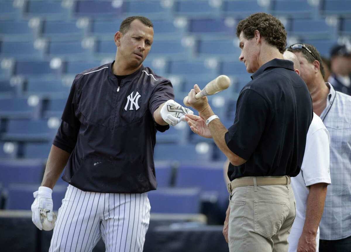 Former New York Yankees outfielder and broadcaster Paul O'Neill, right, inspects Alex Rodriguez's bat after batting practice before a spring training game against the Detroit Tigers on Tuesday in Tampa, Fla.