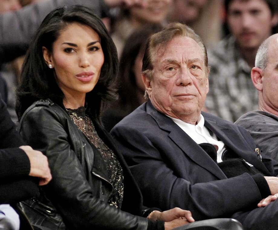 FILE - In this Dec. 19, 2011, file photo, Los Angeles Clippers owner Donald Sterling, right, sits with V. Stiviano as they watch the Clippers play the Los Angeles Lakers during an NBA preseason basketball game in Los Angeles. Sterling's wife, Shelly Sterling, is going after the $2.5 million in real estate and cars her husband lavished on V. Stiviano in a trial scheduled to begin Wednesday, March 25, 2015, in Los Angeles Superior Court. (AP Photo/Danny Moloshok, File) Photo: AP / FR161655 AP