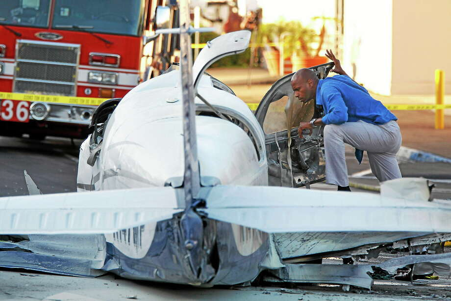 An aviation safety inspector looks inside the cockpit of a small airplane after it crashed in a shopping center parking lot on July 30, 2014 in San Diego. Photo: AP Photo/UT San Diego, Hayne Palmour IV  / UT San Diego