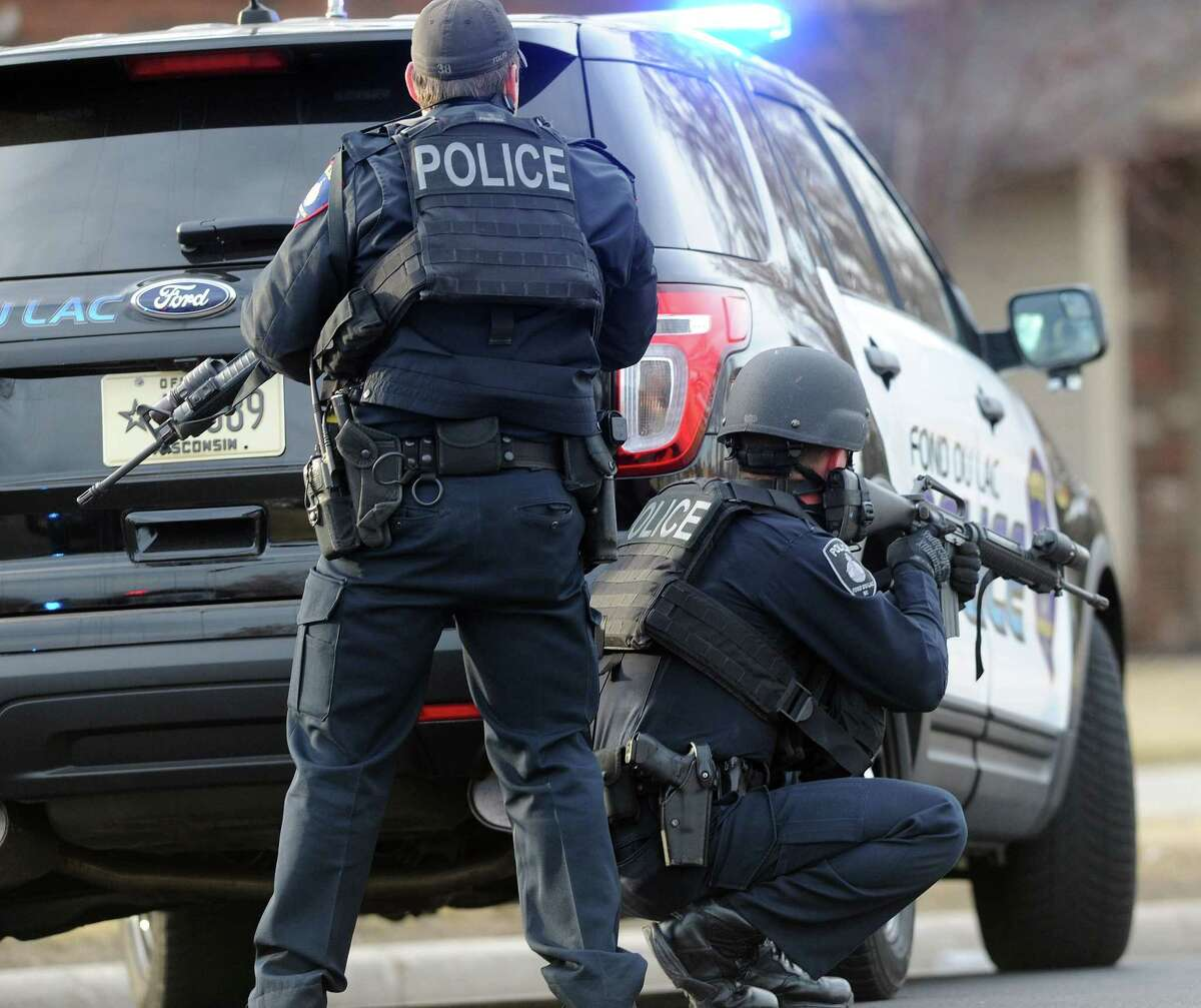In this Tuesday, March 24, 2015 photo, officers work the scene where a Wisconsin State Patrol trooper just three months out of the academy died in a shootout with a bank robbery suspect also believed to have killed another motorist, in Fond du Lac, Wis. The suspect also died in the shootout. (AP Photo/The Reporter, Doug Raflik)