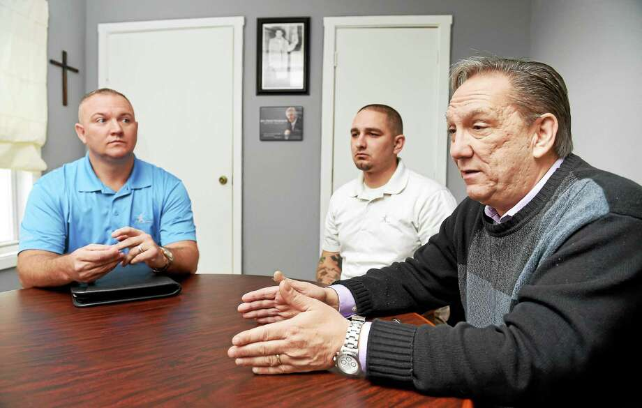 (Arnold Gold-New Haven Register)   Left to right, Michael P. Hayes-Moore, assistant director, and Steve Stokes, program facilitator, listen to Pastor Rick Welch, executive director, being interviewed at Teen Challenge offices in New Haven on 11/19/2015. Photo: Journal Register Co.