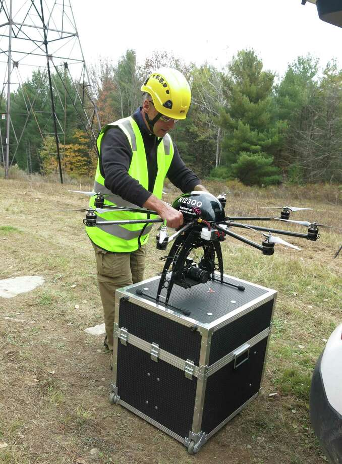 In an Oct. 21, 2015 photo, Bernd Lutz, CEO of Boulder, Colorado-based bizUAS Corp., which provides drone services for utilities and other industries, prepares to demonstrate the use of a Cyberhawk octocopter drone for power line inspections at a New York Power Authority site in the Catskills, near Blenheim, N.Y. Photo: AP Photo/Mary Esch  / AP
