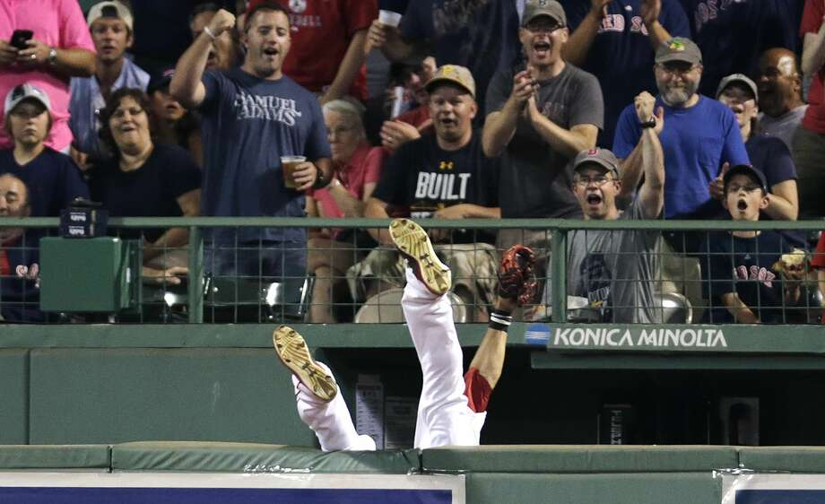 Boston Red Sox center fielder Mookie Betts flips over the wall while trying to catch a fly ball off the bat of the Chicago White Sox's Jose Abreu on Tuesday night. Betts suffered a concussion on the play. Photo: Charles Krupa — The Associated Press  / AP