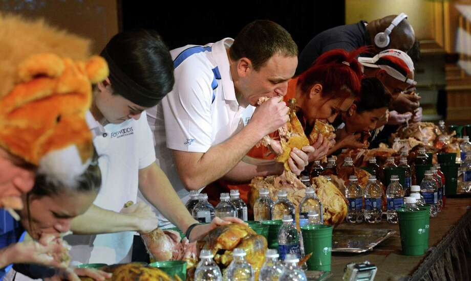 Joey Chestnut, center, and the other eaters participate Saturday in the World Turkey-Eating Championship at Foxwoods Resort and Casino in Mashantucket, Conn. Chestnut won the contest in Connecticut, setting a record by devouring an entire bird. Photo: Associated Press — The Day, Dana Jensen  / The Day
