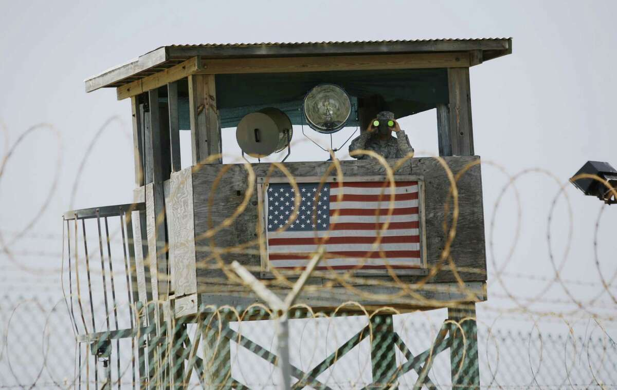 In this May 13, 2008, file photo reviewed by the U.S. Military, a U.S. Army soldier looks through binoculars while standing on a guard tower at Camp 4 in the Guantanamo Bay U.S. Naval Base in Cuba.