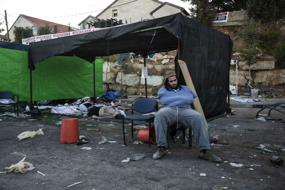 An Israeli settler sleeps in the Jewish settlement of Beit El after a night standoff with police, near the West Bank town of Ramallah, Wednesday, July 29, 2015. Photo: AP Photo/Tsafrir Abayov  / AP