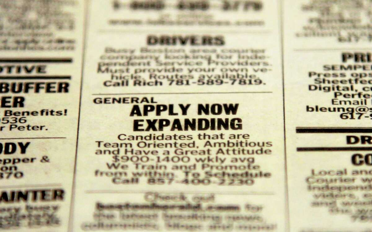 FILE - In this Tuesday, Dec. 11, 2012 file photo, an advertisement in the classified section of the Boston Herald newspaper calls attention to possible employment opportunities in Walpole, Mass. The year 2013 marked a third straight year of modest job growth of 2.1 to 2.2 million jobs, still too few to restore all the jobs lost to the Great Recession, which officially ended more than 4½ years ago. (AP Photo/Steven Senne, File)
