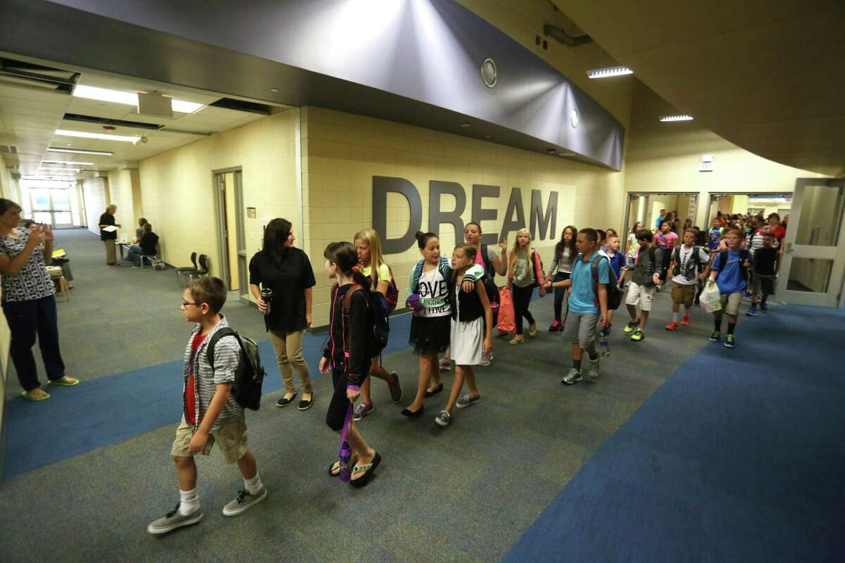 In this Sept. 3, 2014 photo, fifth grade students walk to their classroom for the first time in their new school Plum Creek Elementary in Hutchinson, Kan. A state district court panel expects to rule by late December on whether Kansas is spending enough money on its public schools to provide an adequate education to every child, and even before there's an answer, the lawsuit itself is complicating efforts to close the state's budget shortfalls. (AP Photo/The Hutchinson News, Travis Morisse)